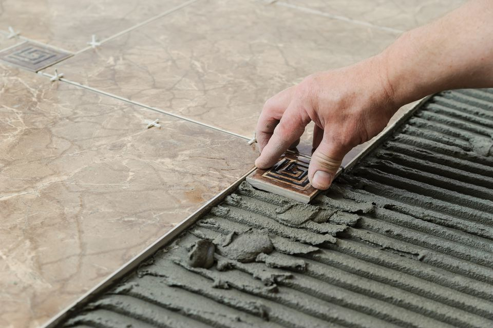 A hand placing a tile on fresh grout