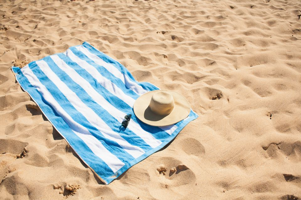 Striped beach towel on sand with hat and glasses