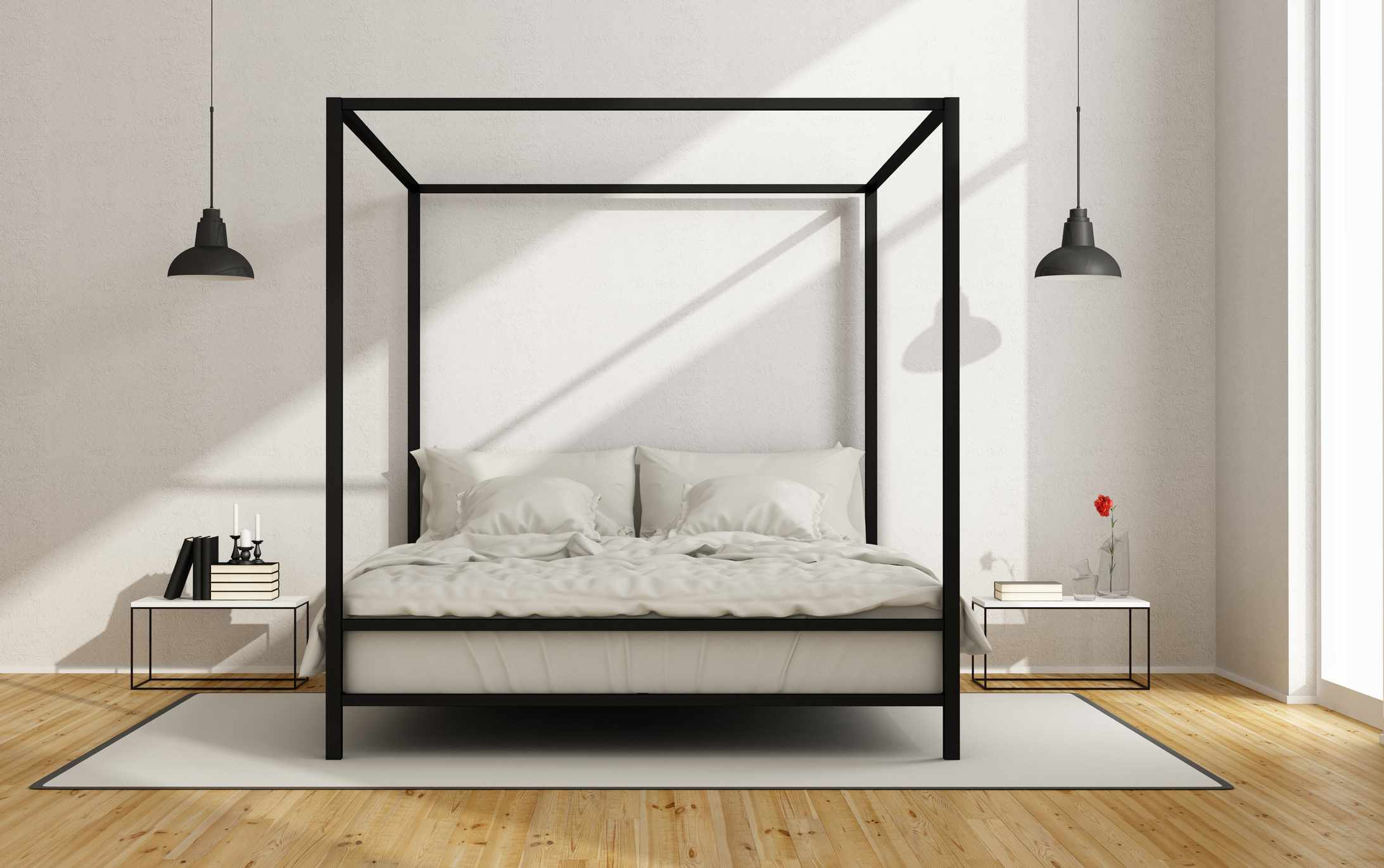 A contemporary black canopy bed frame in a white room.