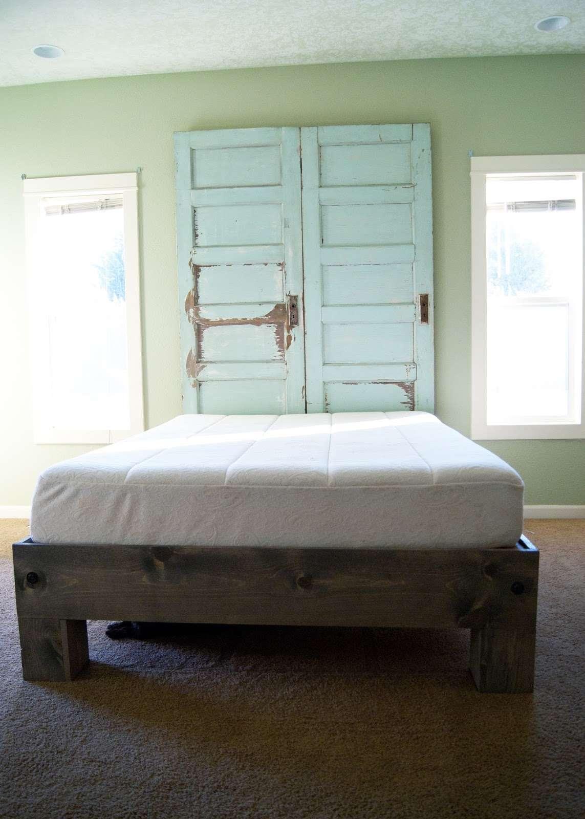 A wooden bed with door headboard