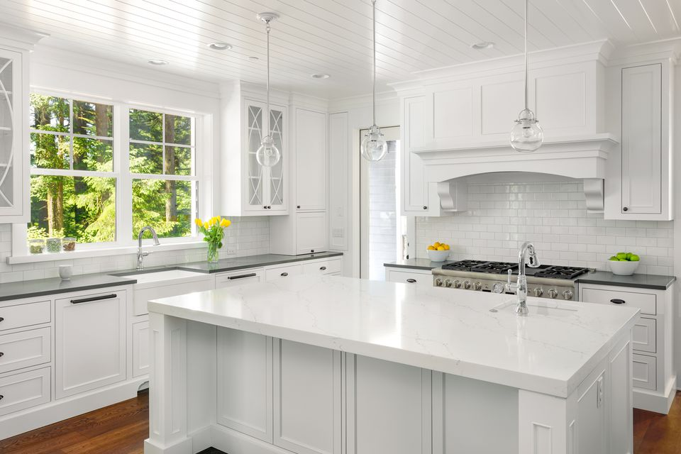 Monochromatic white kitchen with subway tile backsplash and marble countertops