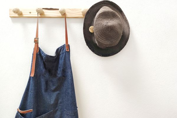 Apron And Hat Hanging Against White Wall