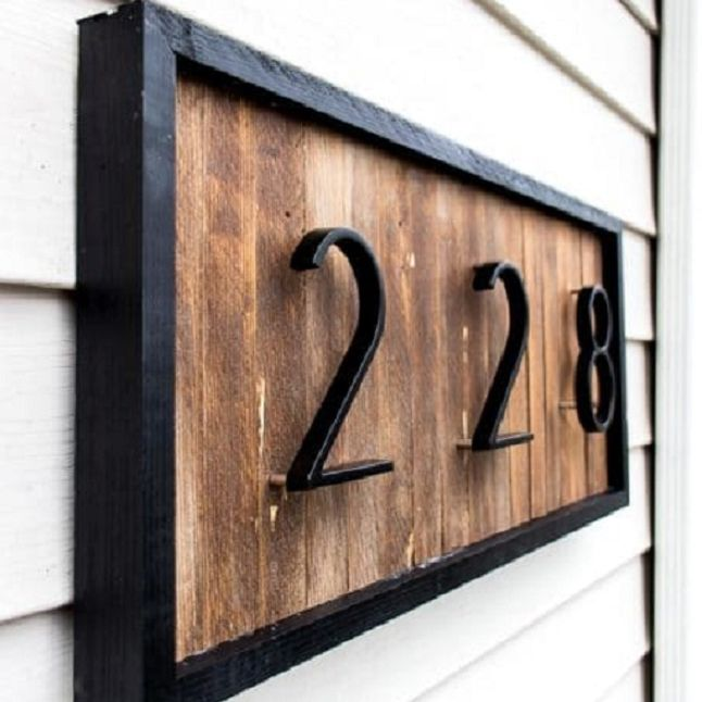 A modern black and wooden address number sign against siding.
