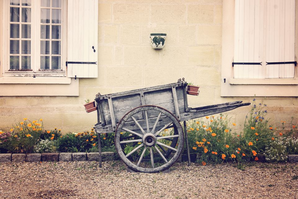 Wooden rustic vintage wheelbarrow in a garden