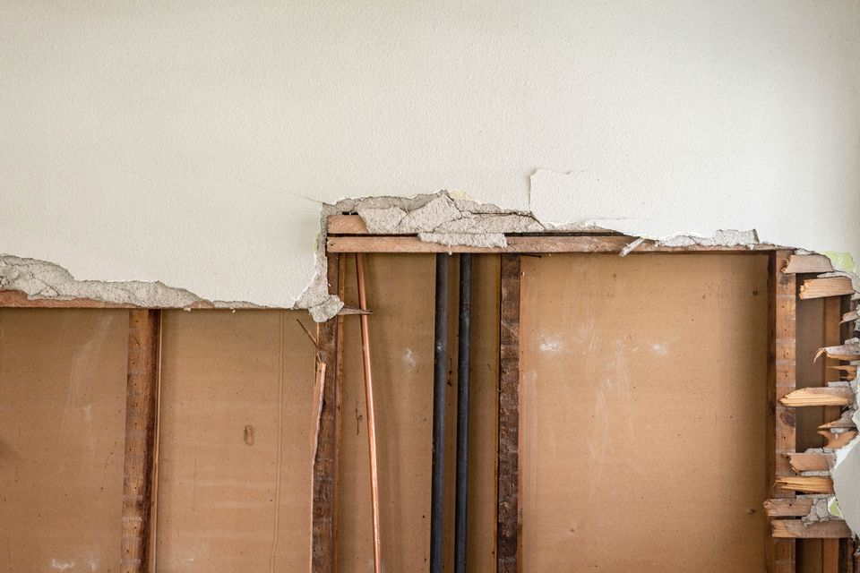 Full interior wall being removed with exposed beams and pipes