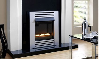 Silver fireplace inset into a black and white wall