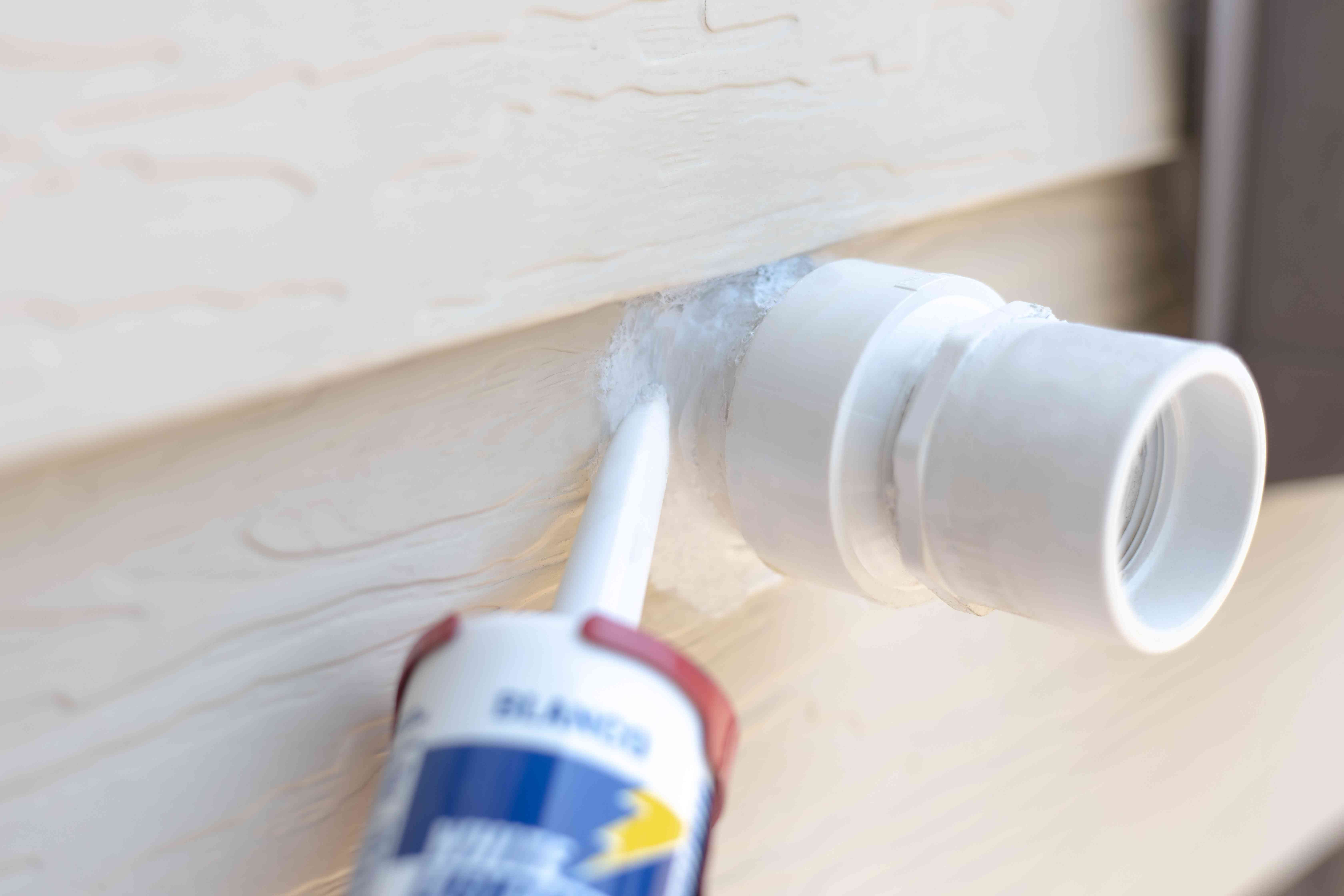 Exposed pipe being ceiled around edges with caulk closeup