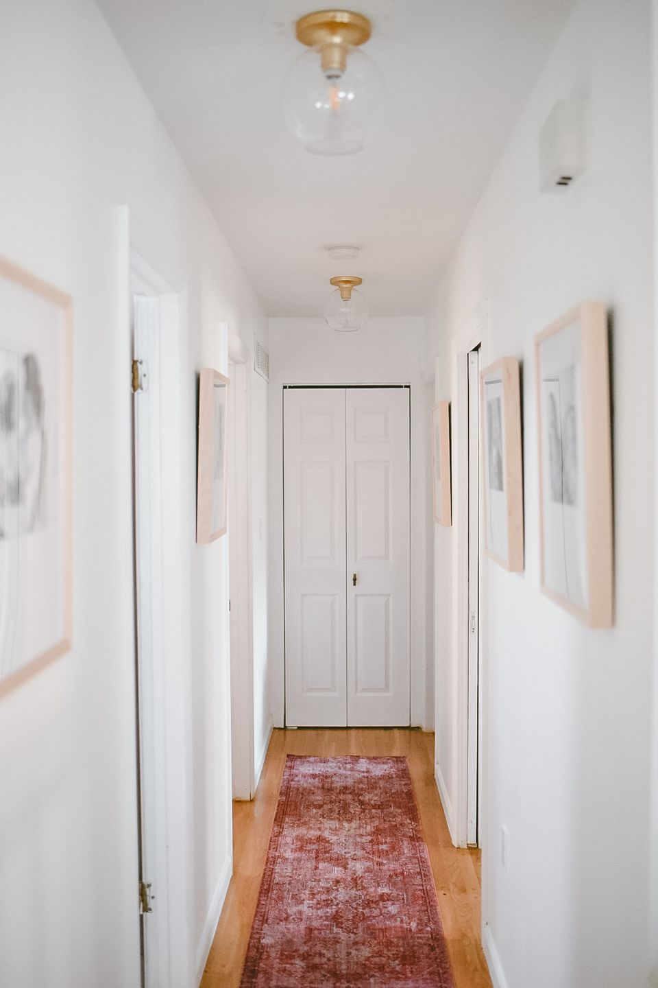 Hallway with a rug and framed pictures