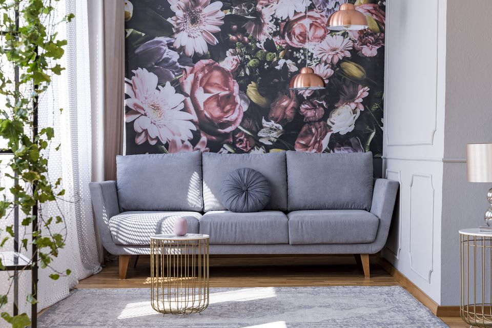 Sunlit, gray sofa by a floral print wall in the nook of a feminine living room interior with golden accessories