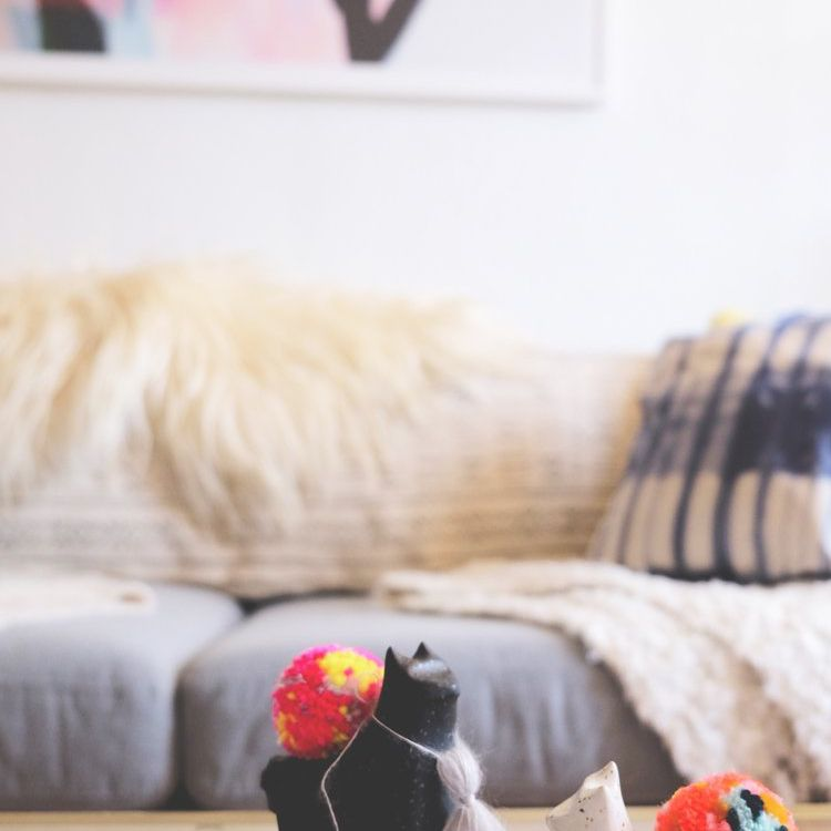 Ceramic alpaca sitting on a table with a couch in the background.