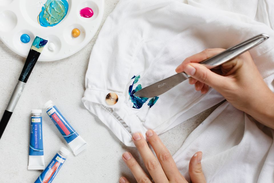 Blue paint removed from white clothing with dull knife next to paint set