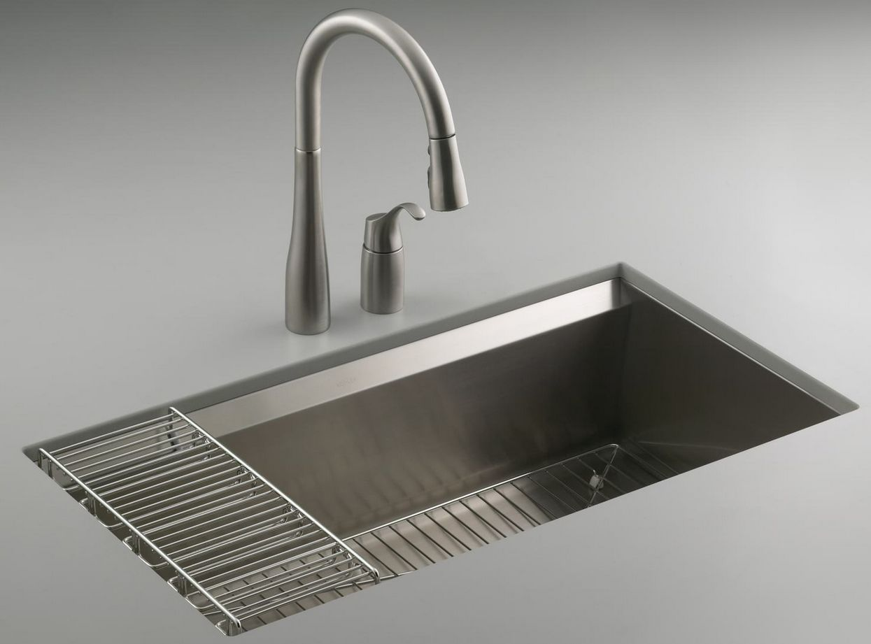 Kohler eight-degree stainless steel sink against a gray background with a faucet.