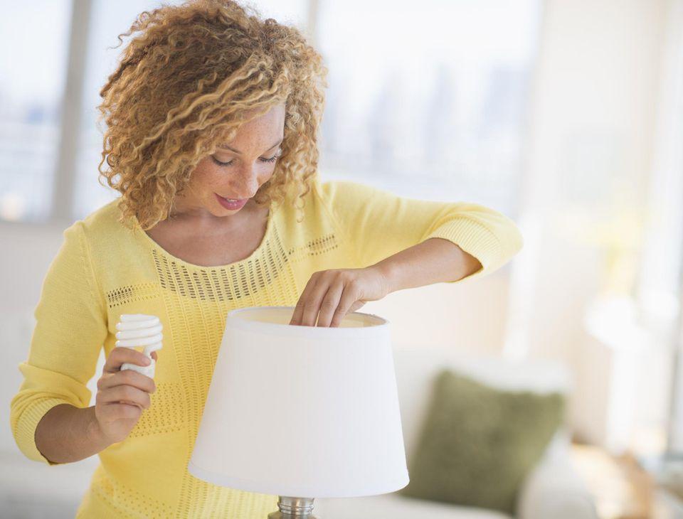 Mujer joven que cambia el bulbo en la lámpara