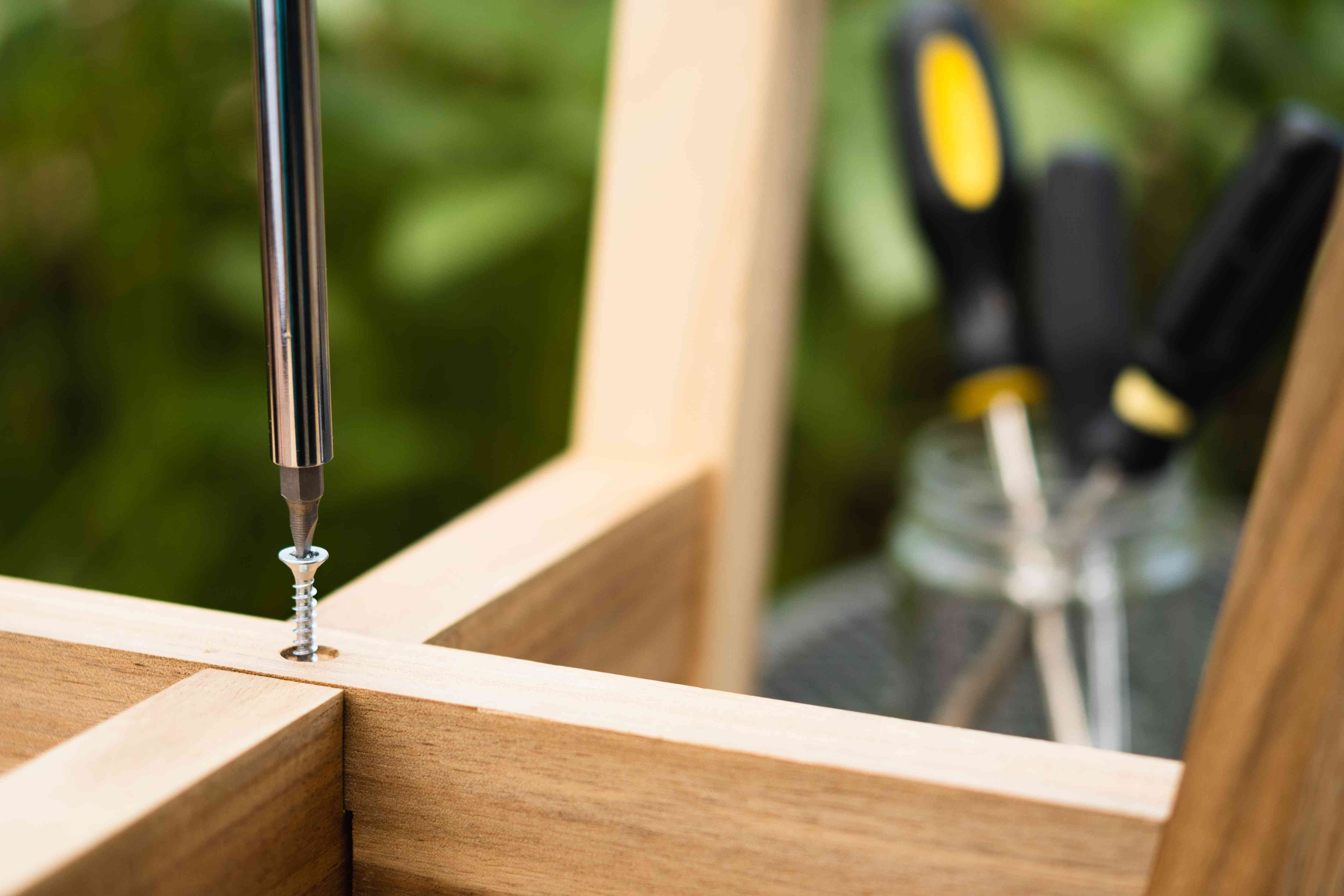 Flat-head screwdriver inserted into stripped screw in wooden fixture