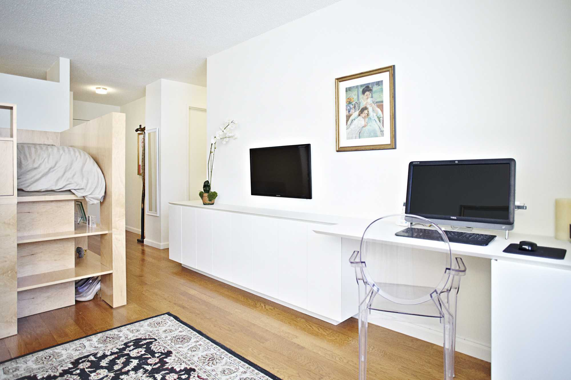 Custom cubby for bed in a studio apartment with television and computer on desk.