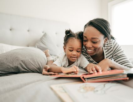 A mother and baby daughter smiling and reading a book while laying on a bed with grey sheets and pillows.