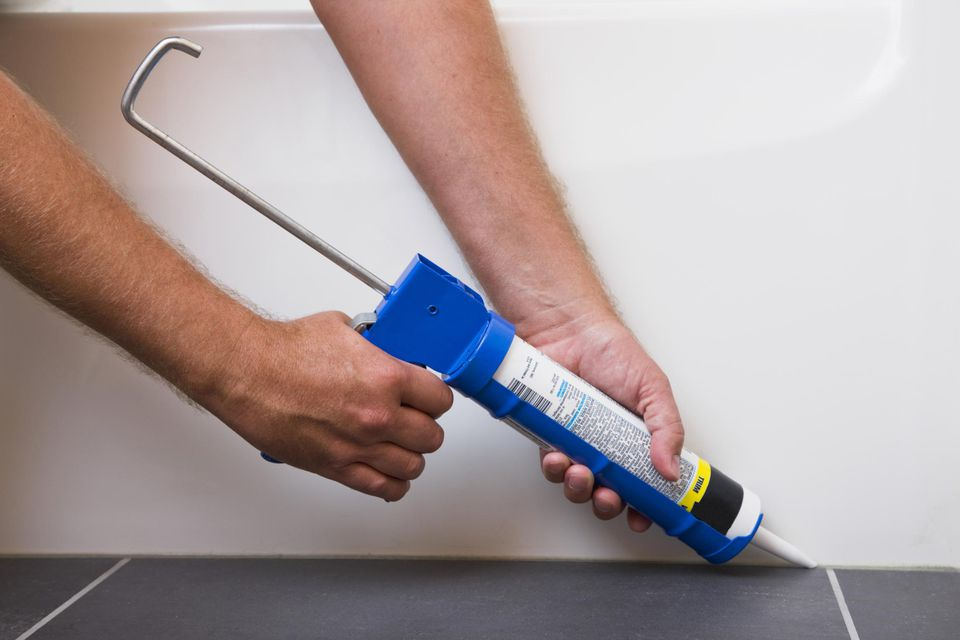 Man using caulking gun, close-up