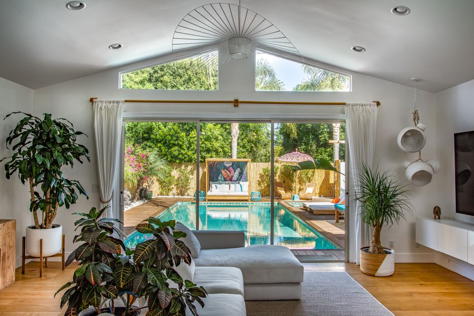 Living space with floor to ceiling window out to pool area