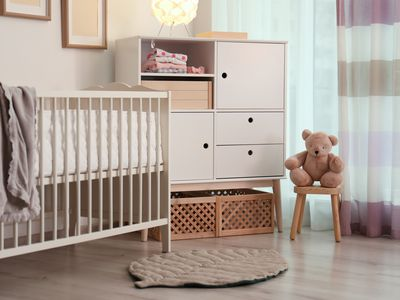 Modern room interior with crib and wooden crates under cupboard. Eco style