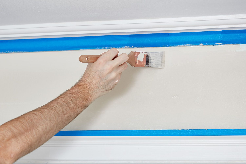 Man using paint brush on wall