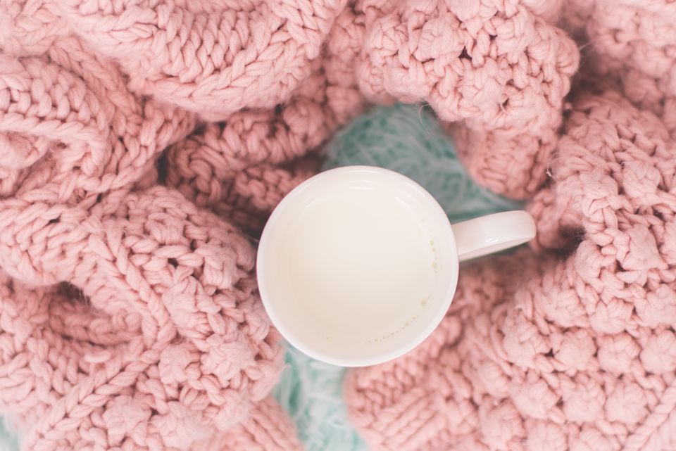 Mug with hot milk and a knitted blanket