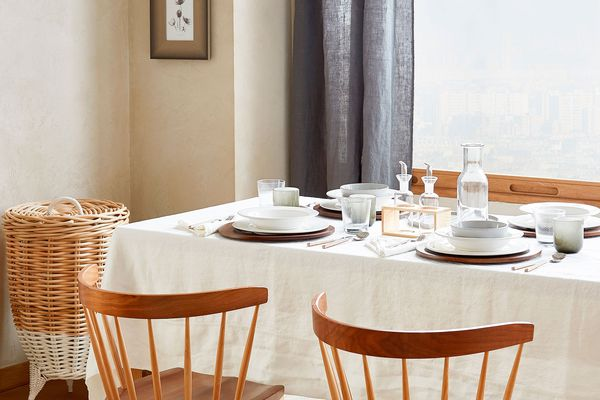 Dining table with tablecloth, table settings, and two wooden chairs near a window with a blue curtain.