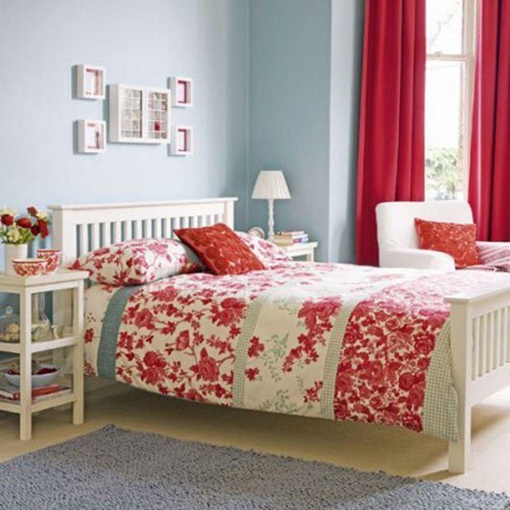 Habitación azul con cortinas rojas y colcha floral roja y blanca.