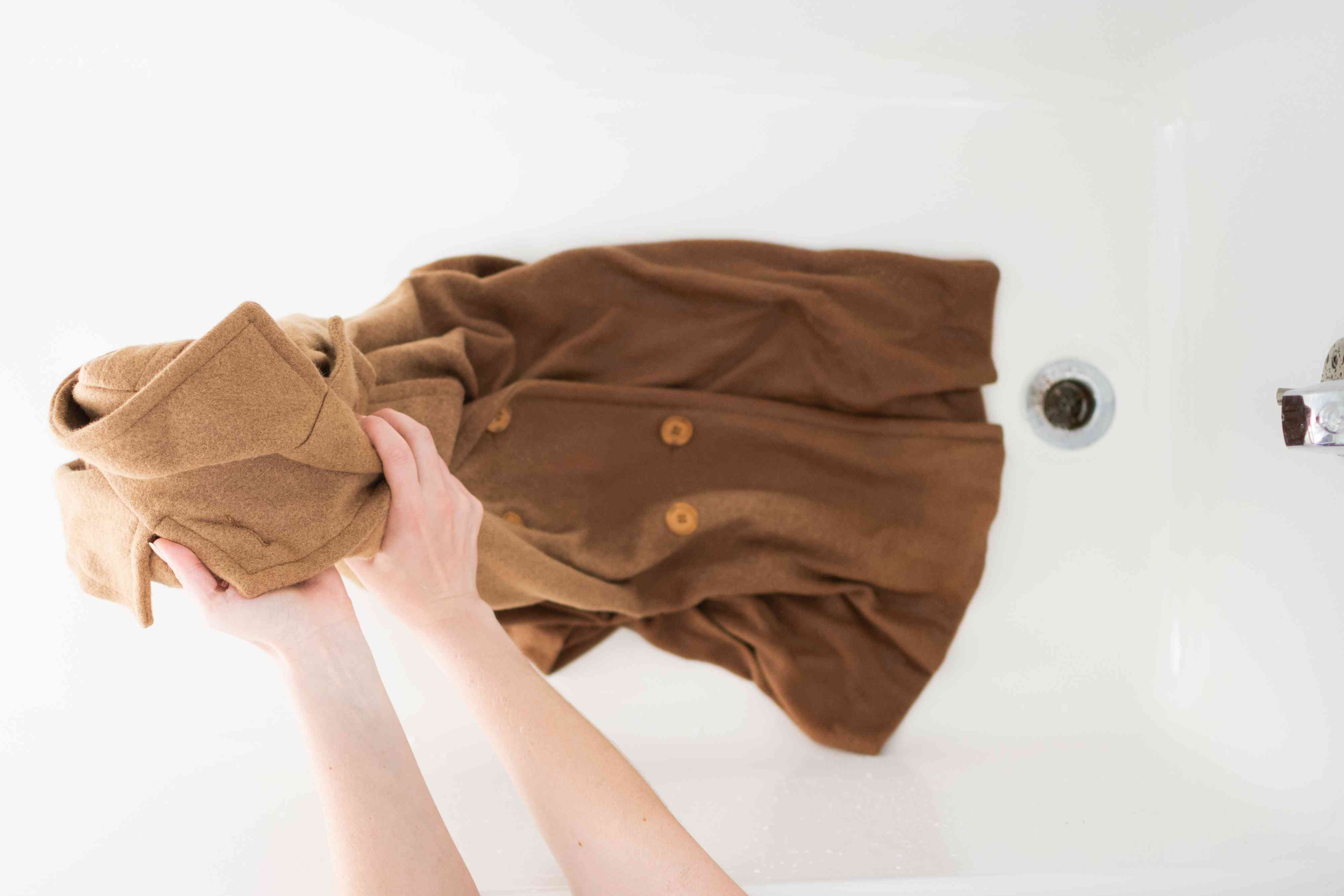 Tan wool coat squeezed gently to remove excess moisture from rinsing