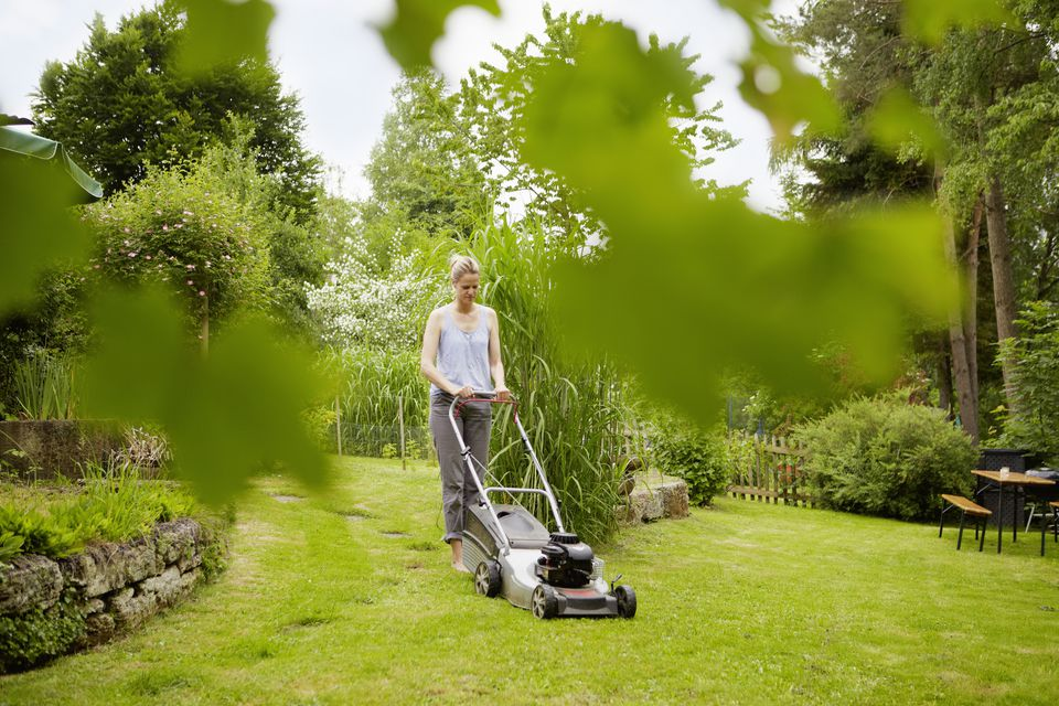 Woman mowing backyard lawn