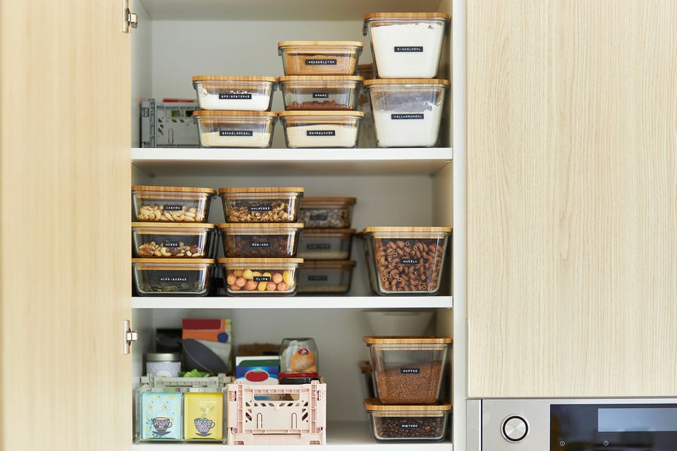 A middle-aged woman tidies up her cupboard in the kitchen and reorganizes everything