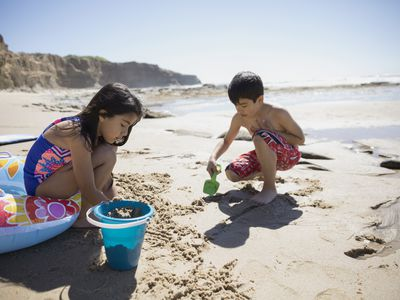 Latino brother and sister playing in the sand on sunny beach