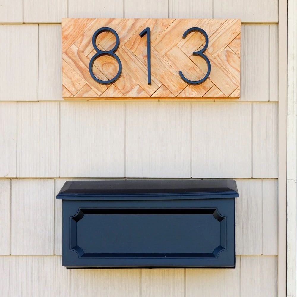 Wood herringbone address sign above a mailbox.