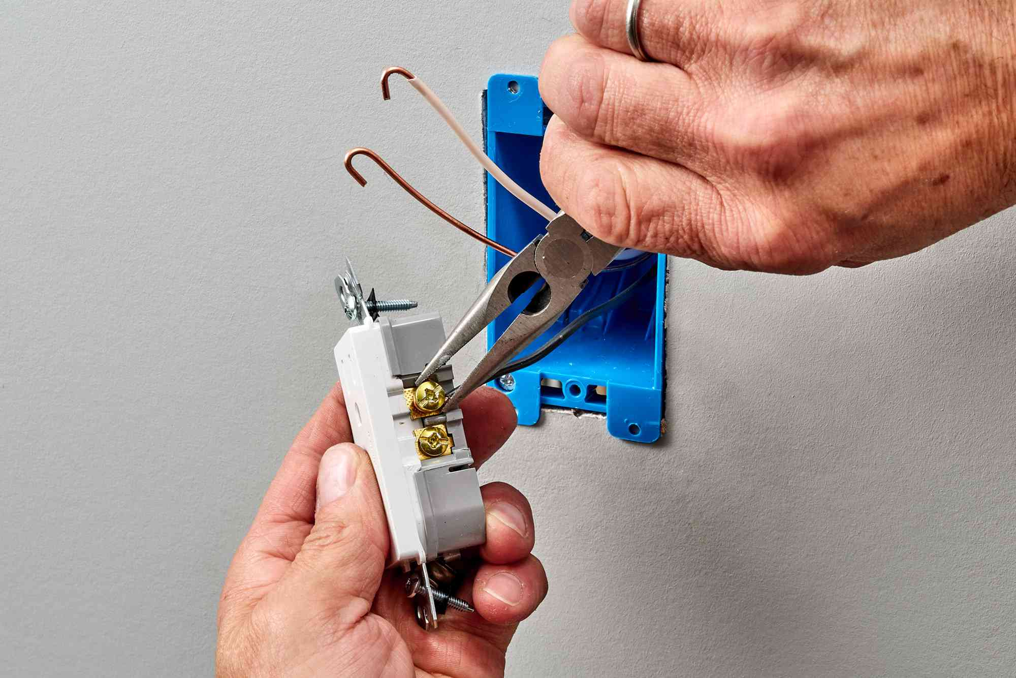 Needlenose pliers securing hooked wires around shank of screw