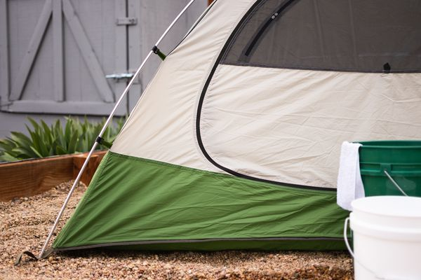Green and cream-colored tent pitched to ground with white and green buckets fro cleaning in front