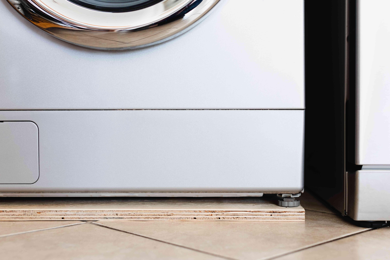Sheet of plywood inserted underneath washing machine to stop vibrating
