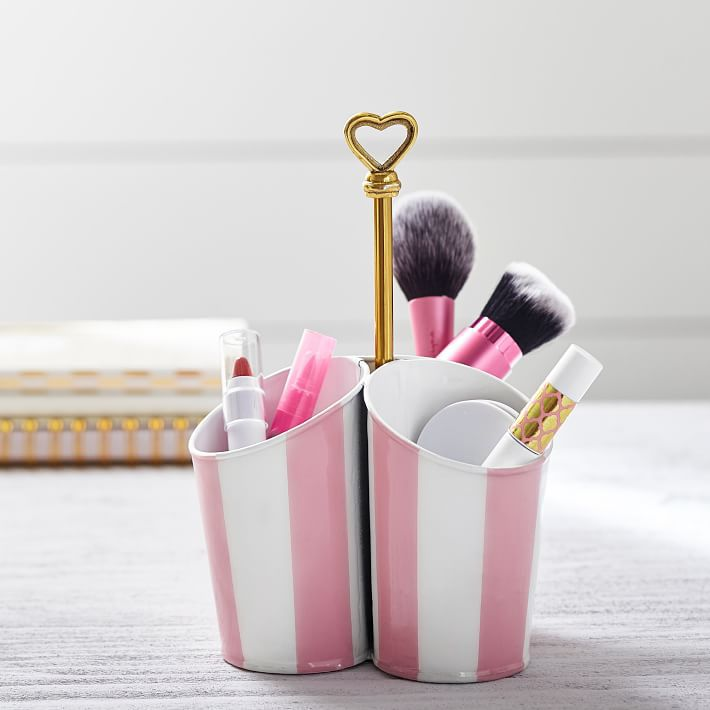 recipientes a rayas de color rosa y blanco con pinceles de maquillaje y lápiz labial