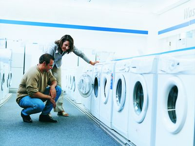 Couple looking at a washing machine in a department store