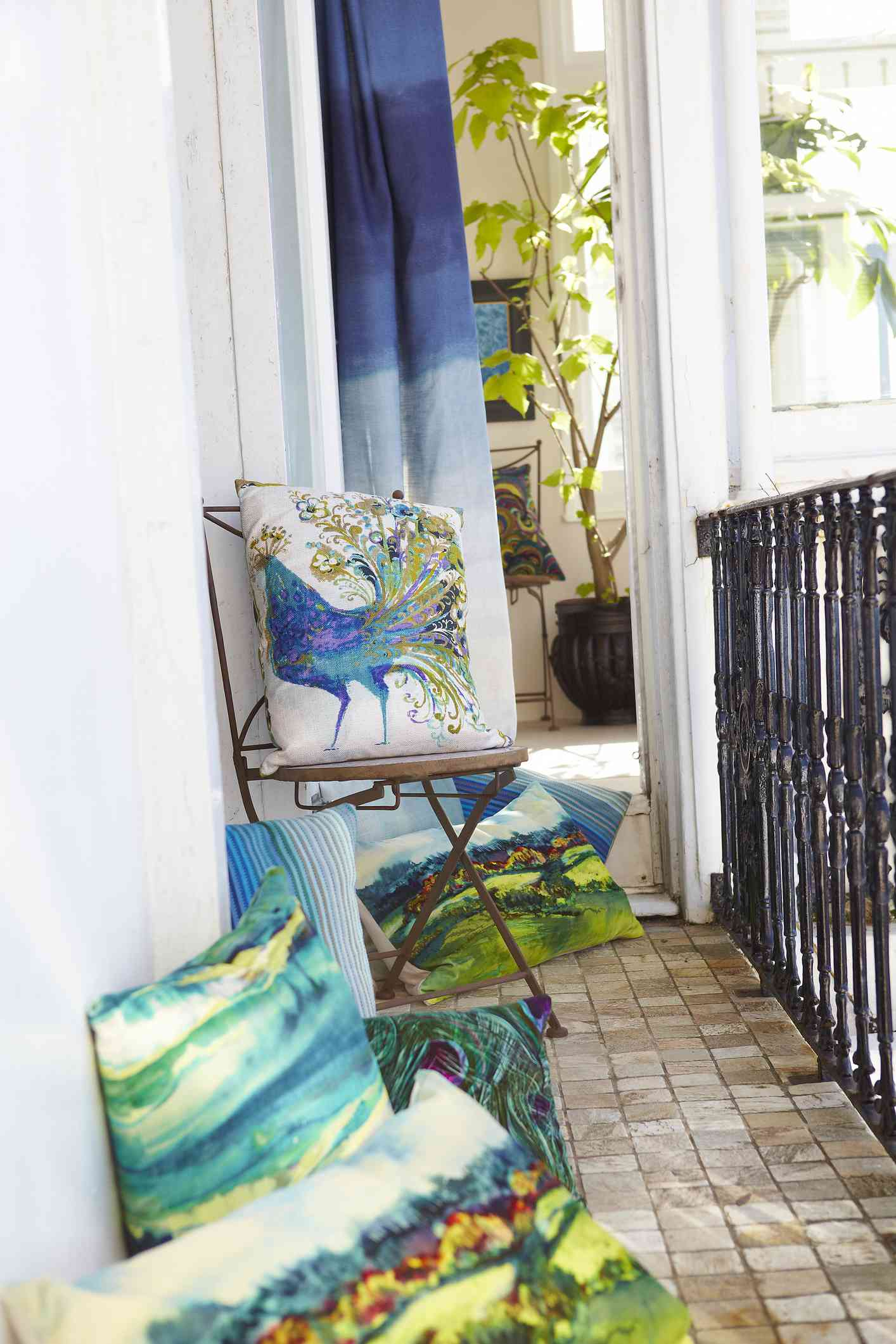 Balcony view with colorful peacock cushions on a chair