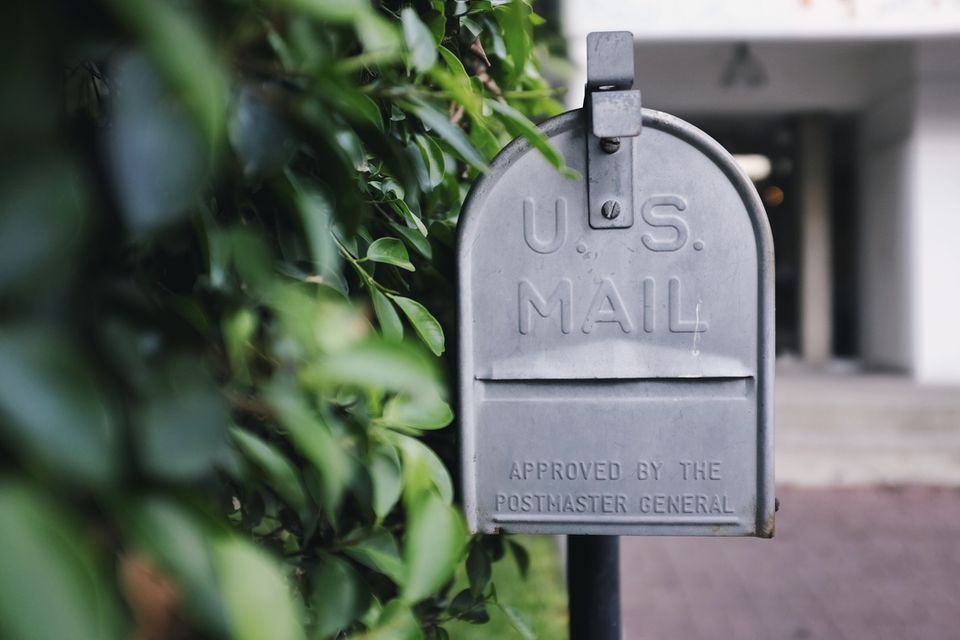 Gray mailbox by a bush