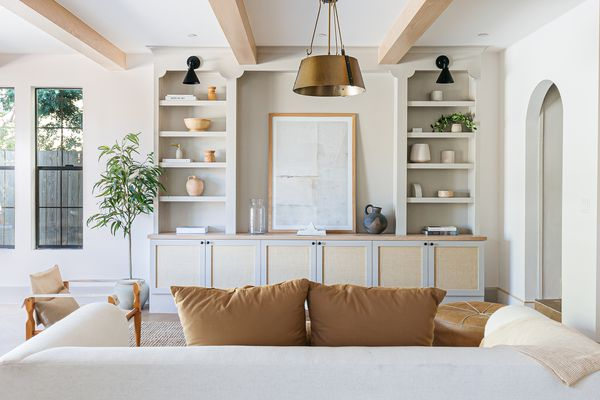 White and cream colored living room with built-in shelving across from white sofa