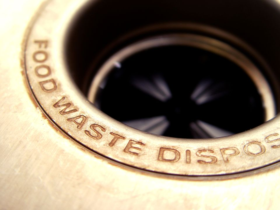 A garbage disposal up-close with the words Food Waste Disposal.