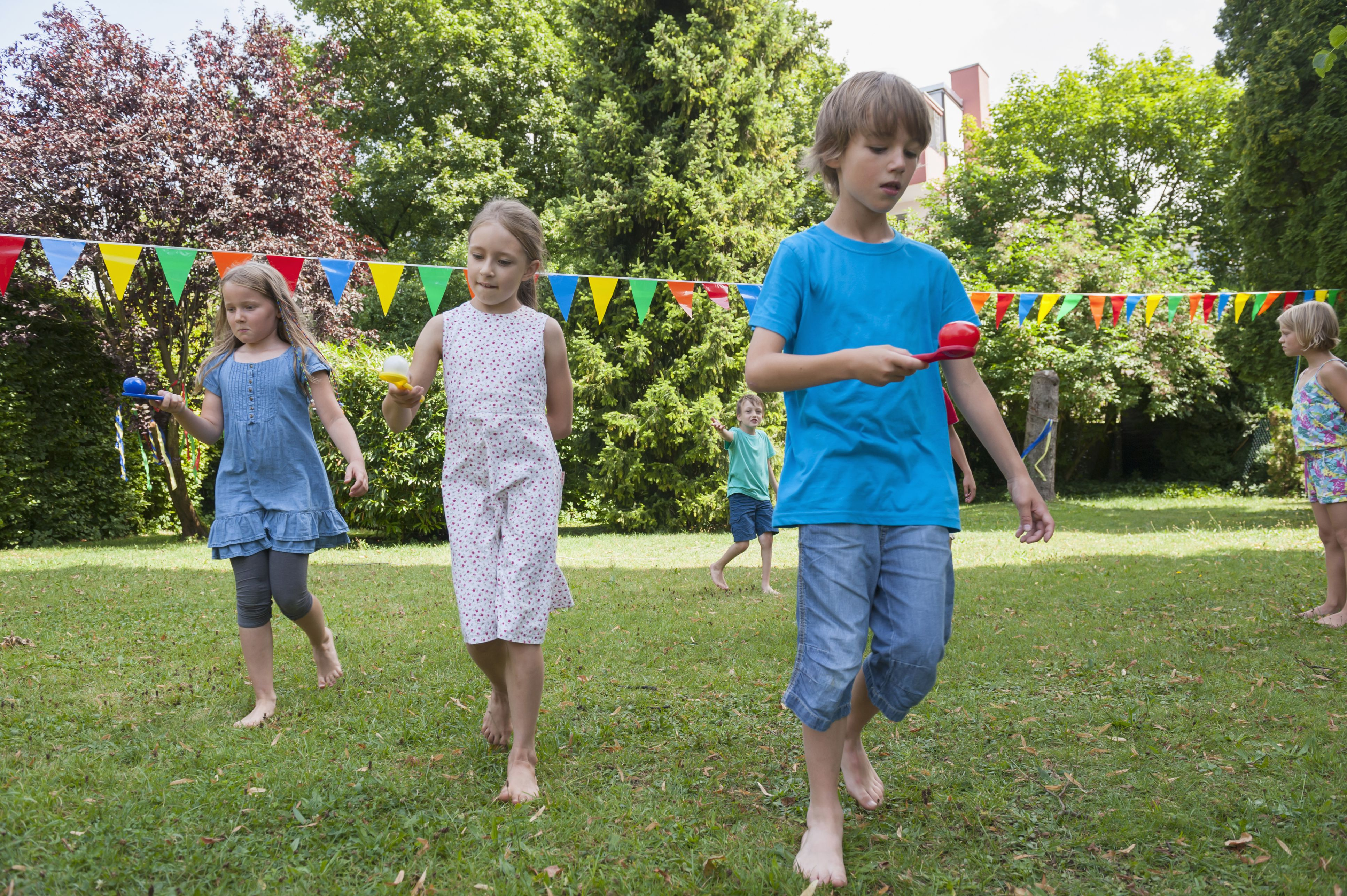 Children having a spoon and egg race in garden on a birthday party