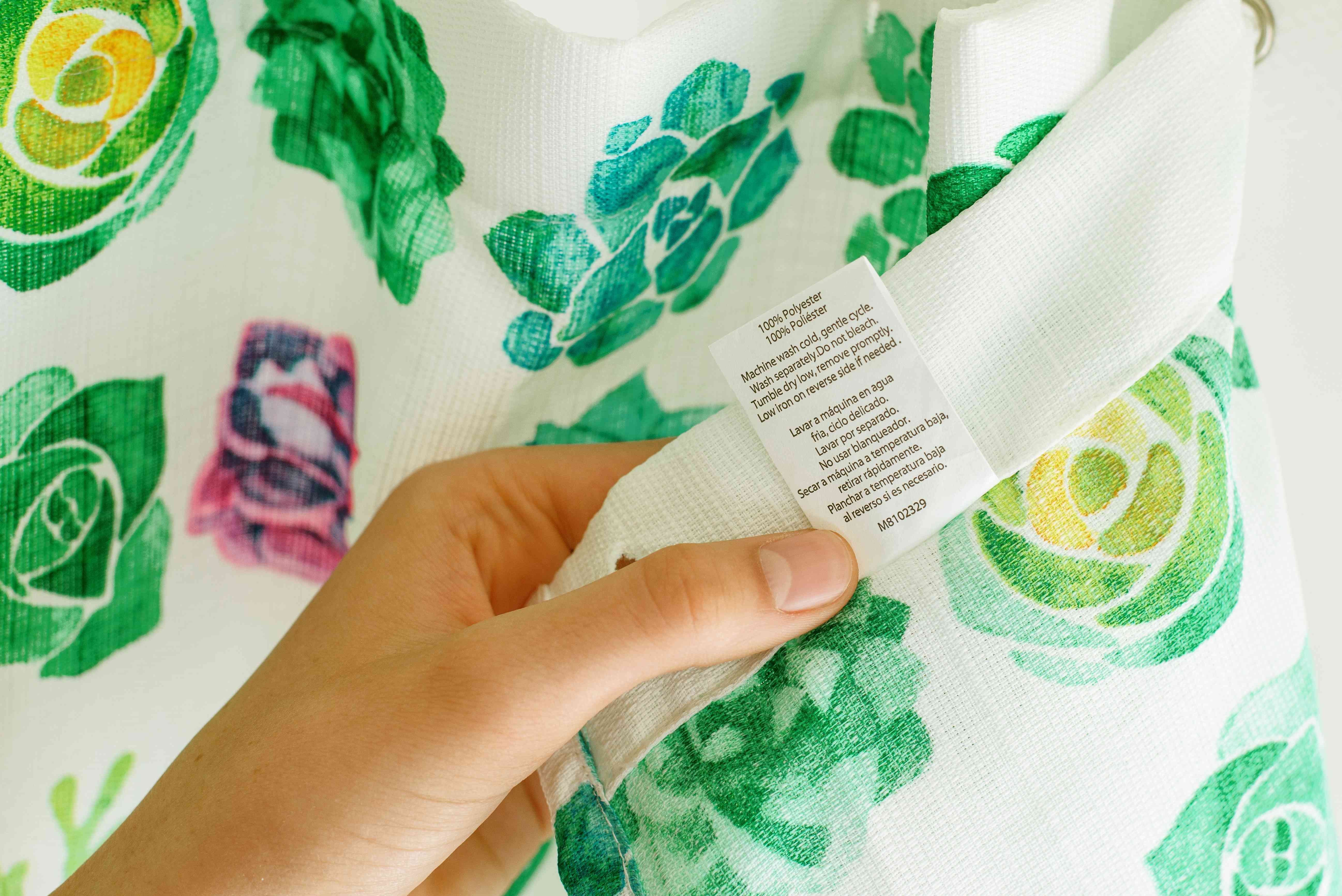 Care label held up by hand on green and white shower curtain