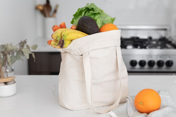 Fabric reusable bag filled with fruits on kitchen counter