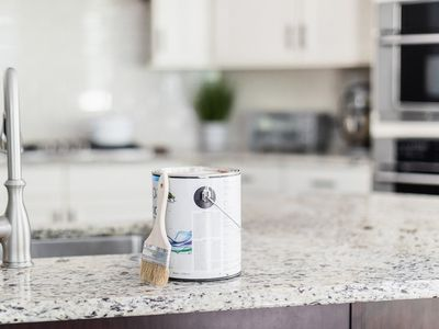 Paint finish in small bucket next to paint brush on marbled kitchen counter