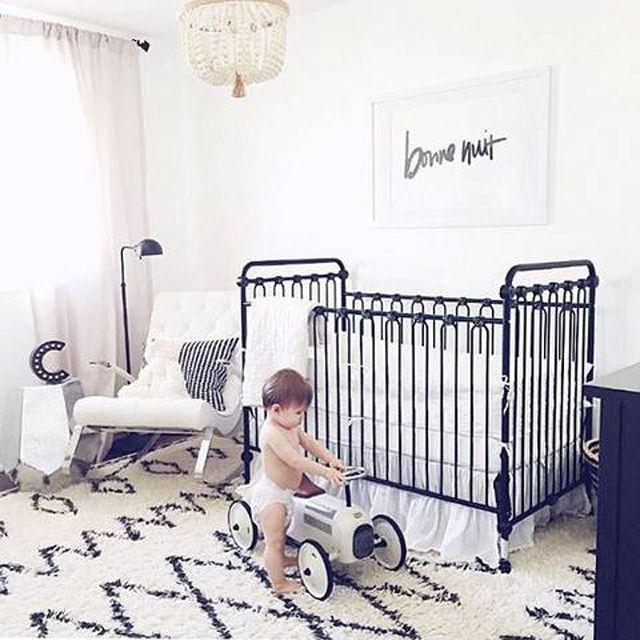 Guardería en blanco y negro con un toque contemporáneo con un niño pequeño en un pañal cerca de un juguete para montar