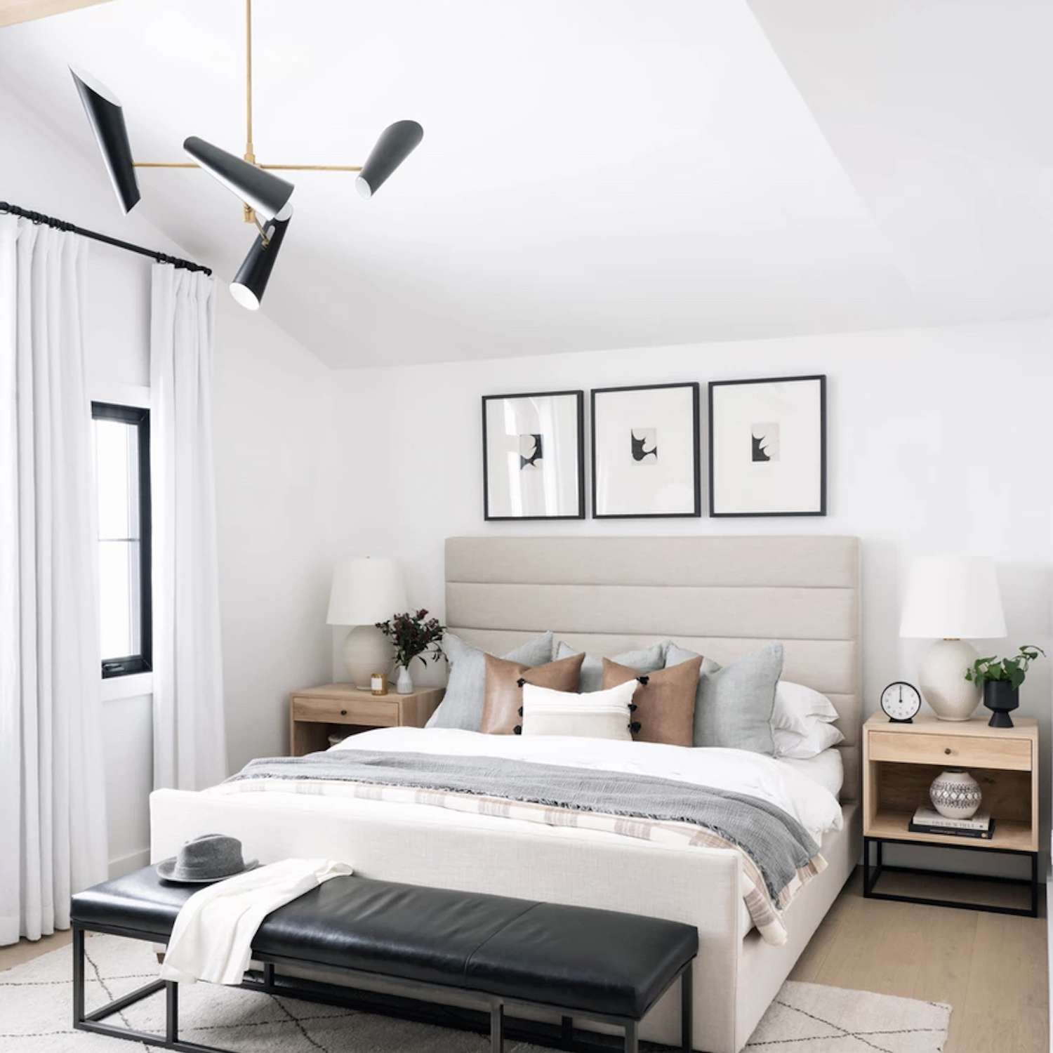 modern bedroom with light gray and brown accents. white area rug. Black leather bench at end of the bed