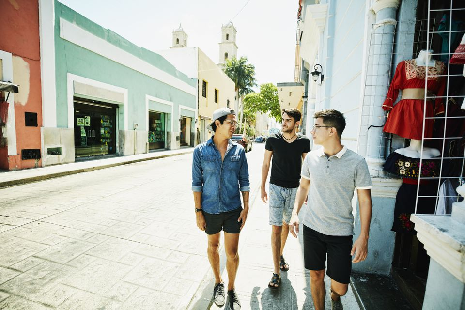 Three friends in discussion while walking on city sidewalk during vacation