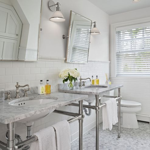 Grey and white bathroom with silver stands over the sink.