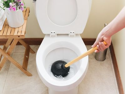 person using a plunger on a clogged toilet